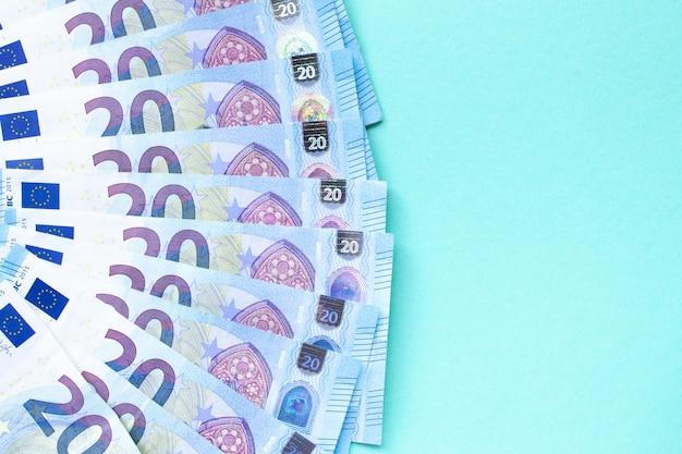 Банкноты номиналом 20 евро выложены на синем фоне с левой стороны. с местом для текста. понятие денег и финансов.