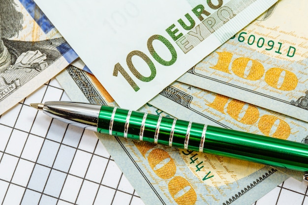 Banknotes one hundred dollars and one hundred euros lay on checkered with a green pen.