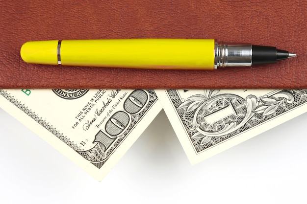 Banknotes and a red pen lying inside the notebook. finance and education