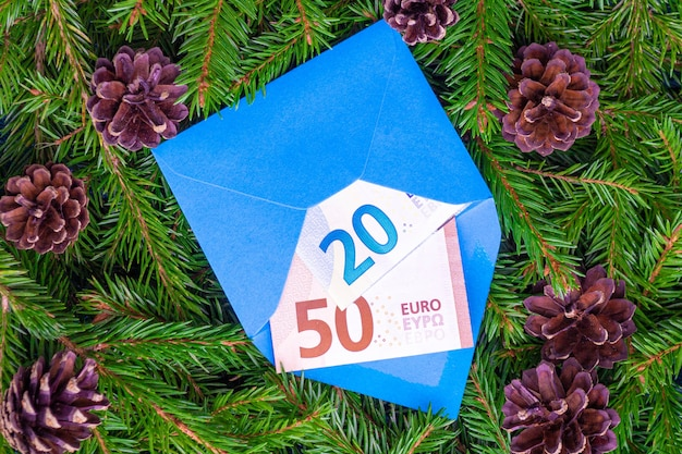 Banknotes of twenty and fifty euro in a blue envelope against the background of christmas tree branches