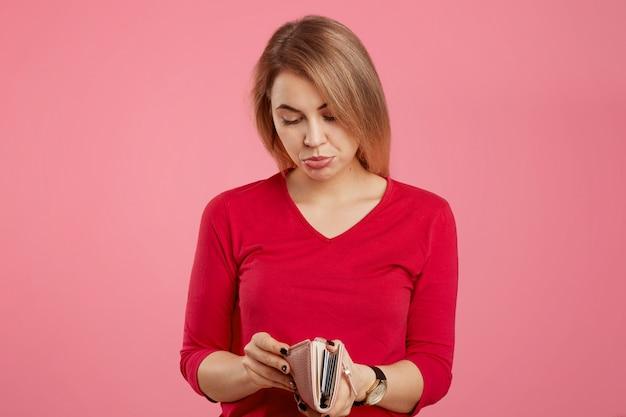 파산 및 금융 개념. 불쾌한 여성 지갑에 불행한 표정으로 보이고, 돈과 많은 빚이 없으며, 입술 아래 입술이 분홍색으로 고립되어 있습니다. 빈 지갑