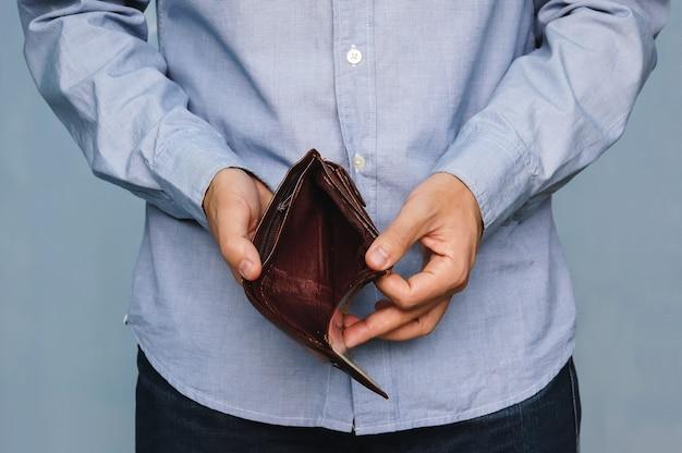 파산 - 비즈니스 사람이 빈 지갑을 들고 있습니다. 남자는 불일치와 돈 부족을 보여주고 대출과 모기지를 지불할 수 없어 빈 지갑을 보여줍니다.