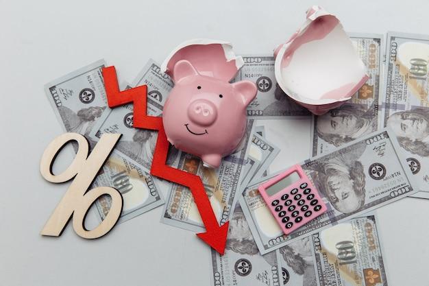 파산 개념 깨진 달러 지폐에 돼지 저금통과 돈 지폐에 아래쪽 화살표