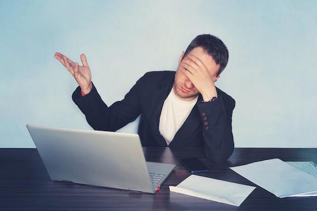 Банкротство предприятия. деловой человек, работающий за компьютером в офисе, держит его за голову рукой и закрывает глаза. понятие о проблемах бизнеса. непонимание недопонимание,