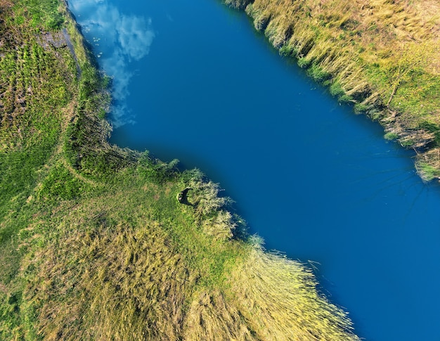 Берега реки покрыты зеленью, на берегу лежит турист.
