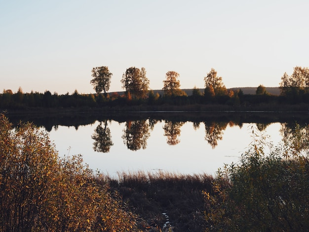 The banks, sky, and trees are reflected in the surface of the water. lake in the autumn season