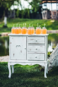 池の近くの自然の中で装飾されたテーブルの上に立っているオレンジジュースの銀行。