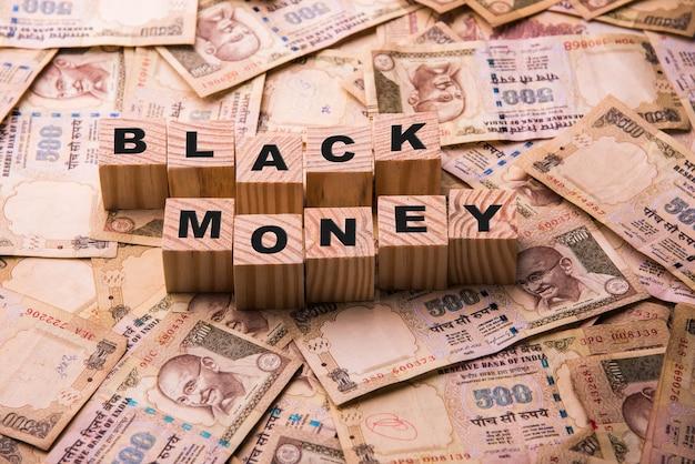 금지된 인도 통화 500루피 지폐는 나무 블록을 사용하여 쓰여진 블랙 머니와 함께 바닥에 누워 있습니다.