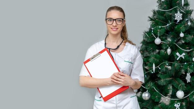 バナー。女性医師がクリスマスツリーのスペースにクリップボードを保持します