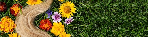 녹색 잔디 머리 건강 개념 천연 재료에 꽃 사이에 금발 머리의 자물쇠를 배너...