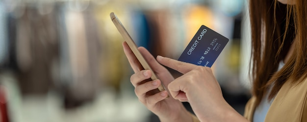 Banner of asian woman using credit card with mobile phone for online shopping in department store