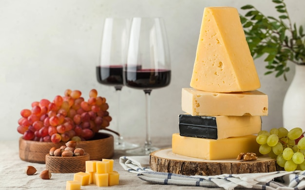 Banner of assorted cheeses with grapes and glasses of red wine on a linen tablecloth.
