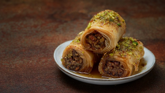 Banner, baklava, close up, middle eastern arab sweet pastry with honey, pistachios, on a dark wall with copy space. selective focus. ramadan, eid concept.