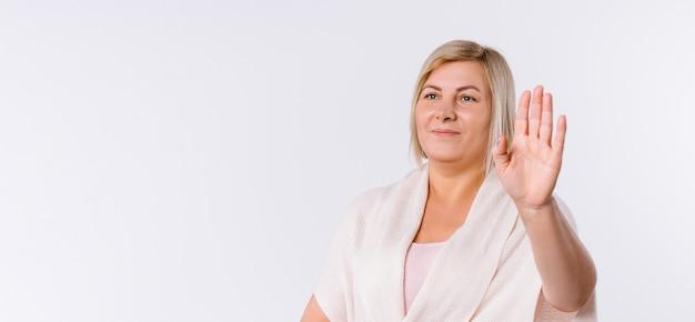 Баннер. белокурая женщина показывает стоп с рукой к камере. белый фон с пустым боковым пространством. фото высокого качества