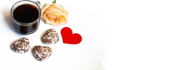 バナー朝食、コーヒー、ハートの形をしたチョコレートケーキ、白い背景の上の黄色いバラ、コピースペース
