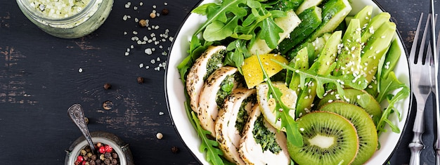 Banner. buddha bowl dish with chicken fillet, avocado, cucumber, fresh arugula salad and sesame. detox and healthy keto diet bowl concept. overhead, top view, flat lay, copy space