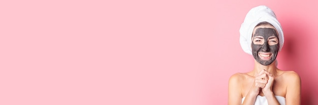 Banner of cheerful smiling young woman with black face mask on a pink background