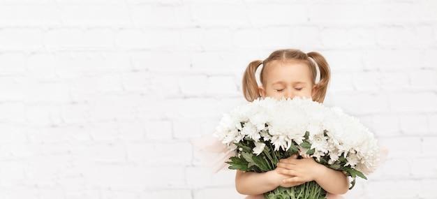 バナーの子は、白いレンガの壁の背景スタジオで隔離の白い花の大きな花束を保持します。