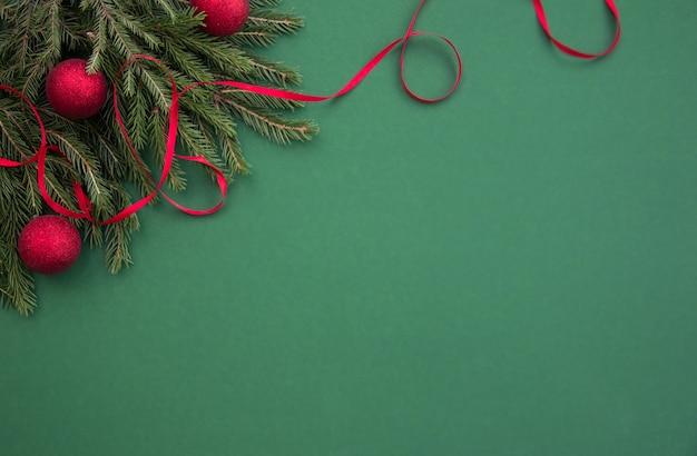 クリスマスツリーの枝と赤い風船とリボンで緑の背景にクリスマスのバナー