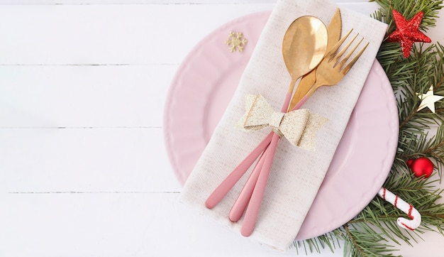 Banner of christmas table setting. pink plate, cutlery with gold bow, fir branches and stars. copy space.