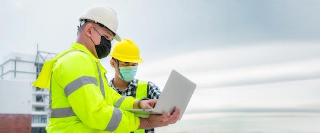 배너 : 마스크를 쓴 토목 기사는 노트북에서 건설 현장 구조와 계획을 검사합니다. 토목 기사는 실제 건설 현장을 검사합니다. 토목 기사는 건물을 검사하기 위해 노트북을 들고 있습니다.