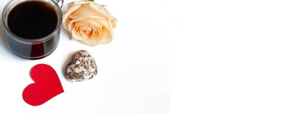 バナーコーヒー、ハートの形をしたチョコレートケーキ、白い背景の上の黄色いバラ、コピースペース