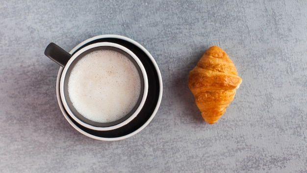 灰色のコンクリートの背景にバナーコーヒーマグカプチーノとクロワッサン。ミニマリズム。甘い食べ物、おいしい朝食。高品質の写真