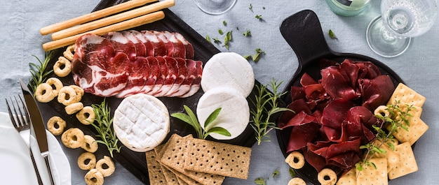 Banner of cold cuts and cheese are served on a tray on a table with white wine, crackers, grissini and taralli with aromatic herbs on a blue linen festive tablecloth.