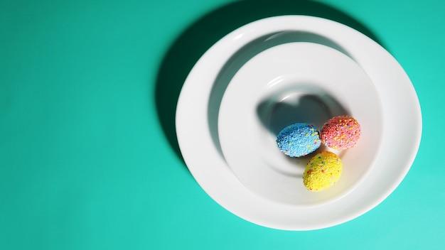 Баннер красочные яйца на тарелке, ярко-зеленый синий фон, концепция пасхи