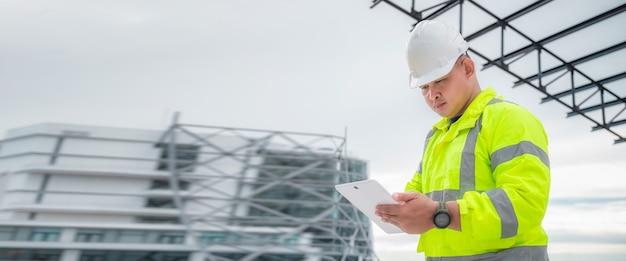 배너 개념:토목 기사는 건설 현장 구조와 계획을 태블릿으로 검사합니다. 토목 기사는 실제 건설 현장을 검사합니다. 토목 기사는 건물을 검사하기 위해 태블릿을 들고 있습니다.