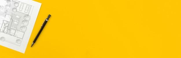 バナーの建設と建築家のデザインコンセプト。ペンでビジネスデスクトップ上の住宅の建物の図面と建築の青写真。黄色の背景とコピースペースのある上面写真