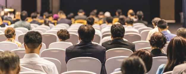 会議場のステージで聴衆を聴くスピーカーの背面図のバナーカバーページ