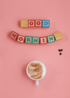 Banner of a cup of coffee and inscription good morning on pink background