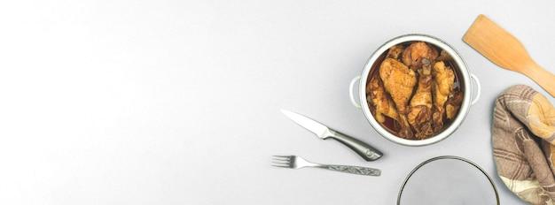Баннер концепция приготовления ужина, жареный чичен в кастрюле на белом и серебряном фоне, кухонное рабочее пространство, вид сверху, полотенце, вилка и деревянная ложка