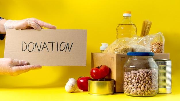 Banner.donation。黄色の背景に検疫隔離期間の食糧供給危機食糧在庫。米、エンドウ豆、シリアル、缶詰、油、野菜、マスク、消毒剤。食べ物の出前。対処スペース。