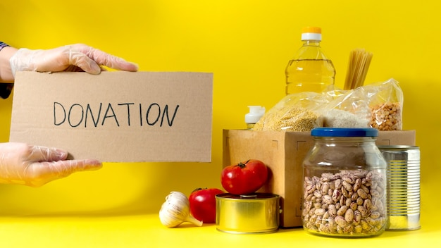 Banner.donation. food supplies crisis food stock for quarantine isolation period on yellow background. rice, peas, cereals, canned food, oil, vegetables, mask, sanitizer. food delivery. cope space.