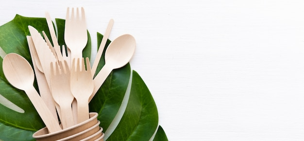 Banner eco friendly disposable kitchenware utensils on white background. wooden forks and spoons in paper cup. ecology, zero waste concept. copyspace