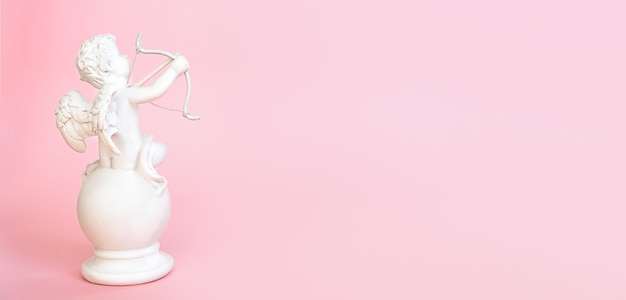 バナー。ピンクの背景に弓を持つ天使キューピッドの置物。バレンタイン・デー。コピースペース