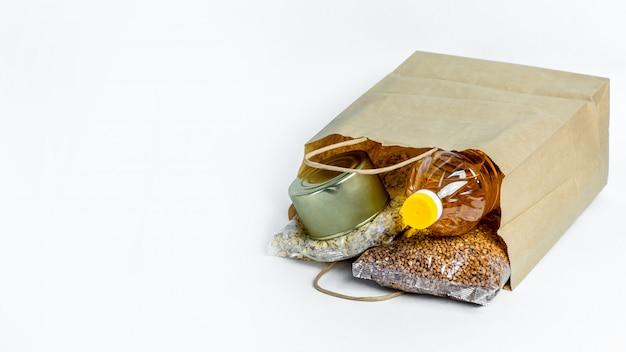 バナー。白い背景で隔離の寄付のための紙袋に食べ物。検疫隔離期間中の必須商品の危機防止在庫。フードデリバリー、コロナウイルス。食糧不足。