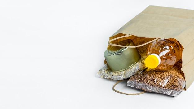 バナー。白い背景で隔離の寄付のための紙袋に食べ物。必須商品の危機対応在庫。