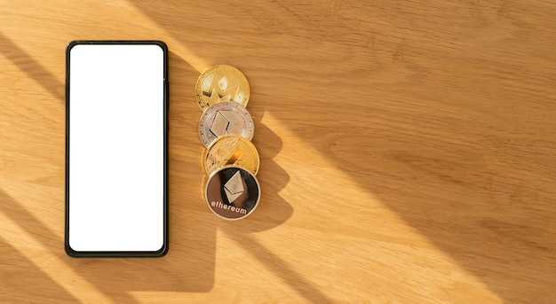 モックアップ電話スクリーン、ビットコイン、イーサリアム、木の表面の背景にコピースペースを備えた暗号通貨広告バナーのバナー。