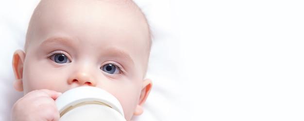 バナーフォーマット。赤ちゃんの牛乳瓶を持つ白人の幼児。閉じる。スペースをコピーします。赤ちゃんの目に焦点を当てます。人工給餌。粉ミルク。