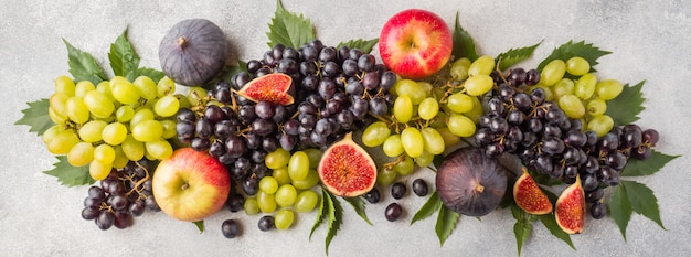 Banner of fresh autumn fruits. grapes black and green, figs and leaves on a grey table.