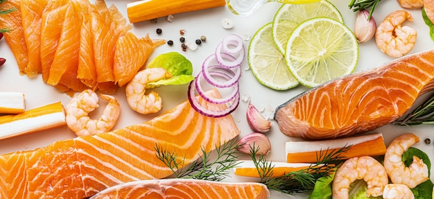 Banner of fresh seafood on table with spices, vegetables and olive oil: fresh and smoked salmon, shrimp and crab sticks for a supermarket or fish sushi restaurant.