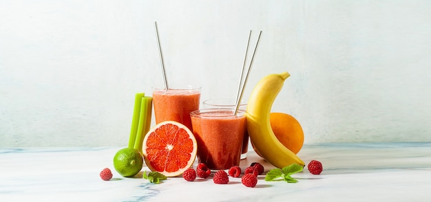 Banner of fresh smoothie juice in glasses with metal tubes on the table and ingredients. healthly food