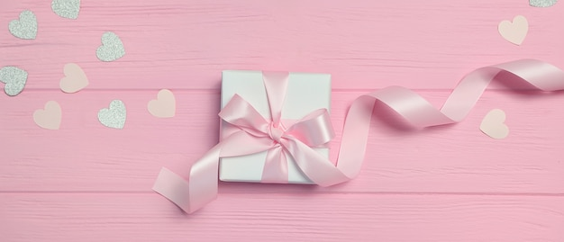 Banner gift box with ribbon and confetti in form of heart on pink wooden background with place for your text.