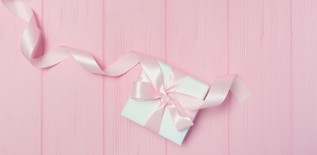 Banner gift box with ribbon on pink wooden background with place for your text