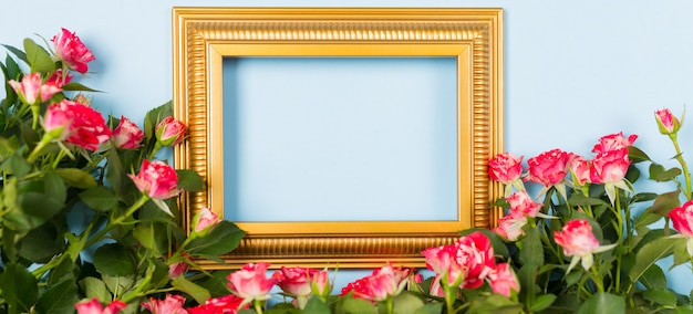Banner golden frame empty blank picture surrounded spray red roses on blue background.
