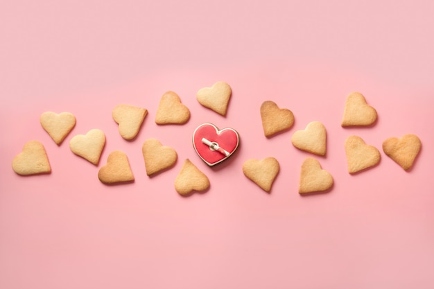 Banner of homemade heart shaped cookies and love letter on pink.