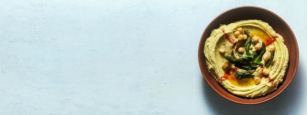 Banner of hummus with green asparagus. spring alternative recipe